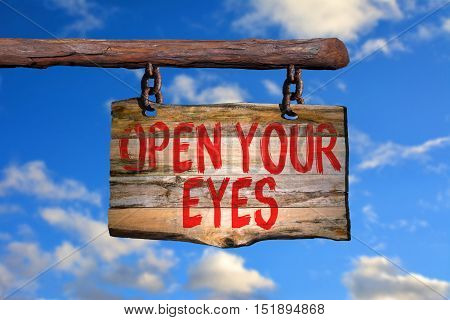 Open your eyes motivational phrase sign on old wood with blurred background