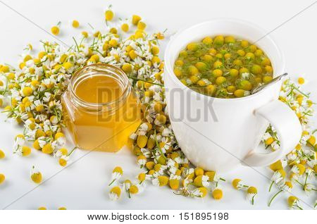 camomile tea with honey on white background