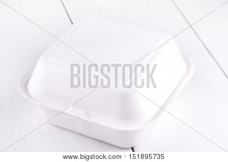 White food box packaging for hamburger lunch fast food burger sandwich. Product pack on white wooden table