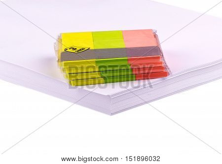 collection of colorful post it paper note on a stack of white paper. Empty colorful post its on on a stack of white paper