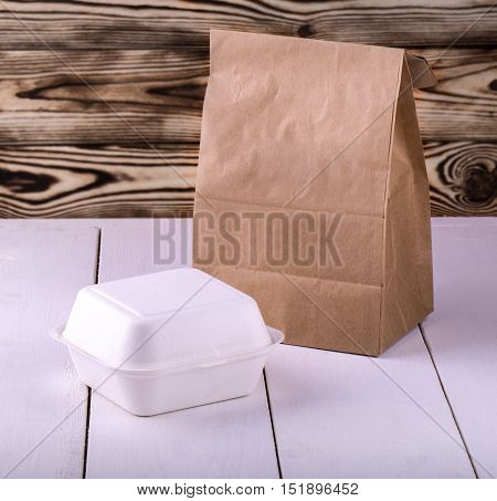 paper shopping bag and container for breakfast on white wooden table
