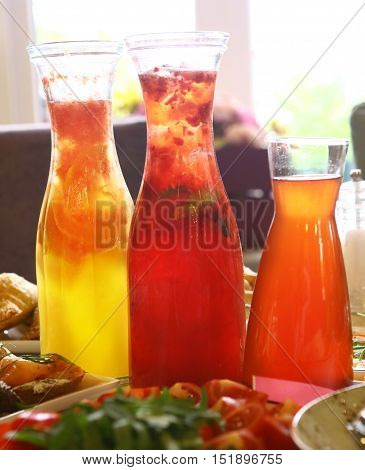 transparent glass jars with fruit drink on the servised restaurant table close up photo