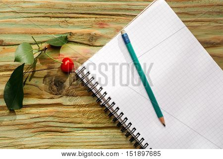 Red cherry with green leaves graphite pencil on white open paper diary on wooden background copy space
