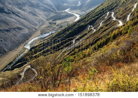 The picturesque top view on the steep winding gravel road through the pass going up the mountain the valley between the mountains and the river