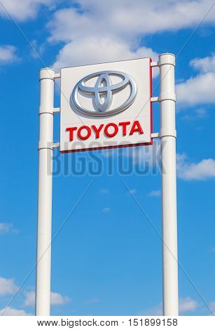 SAMARA RUSSIA - MAY 11 2016: Toyota automotive dealership sign against the blue sky background. Toyota is the world's market leader in sales of hybrid electric vehicles