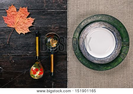 Still life with Russian traditional painted spoons, plates and maple leaf on the half covered table. Flat lay