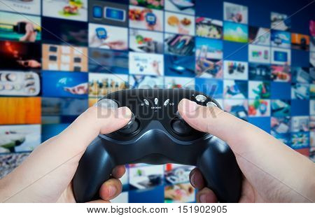 Gamer holding game pad in hands. Game play controller with streaming multimedia in background concept
