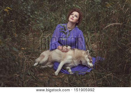 Girl holds a dead dog Husky they in the fairy forest.