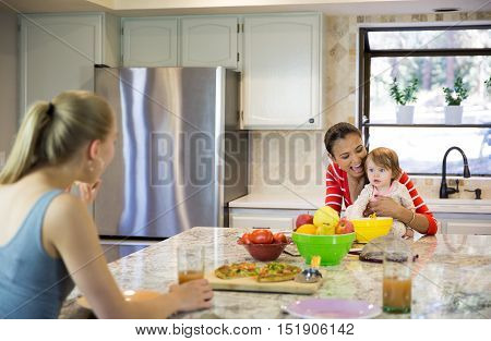Two Beautiful Young Women And Little Baby Girl In The Kitchen