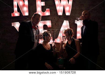 Four happy friends drink white wine near illuminated letters (New Year) in dark studio
