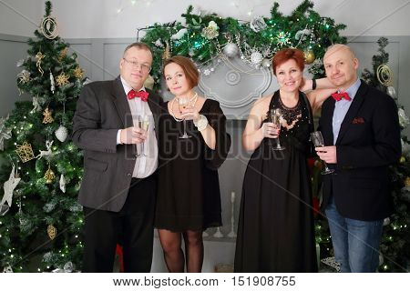 Two happy middleaged couple stand with wine during christmas evening