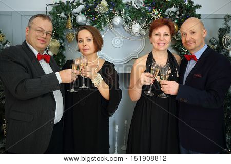 Two happy couple drink wine during christmas evening in room with decorations