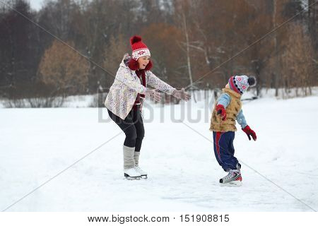 Happy mother catches her cute little son skating on ice in winter day