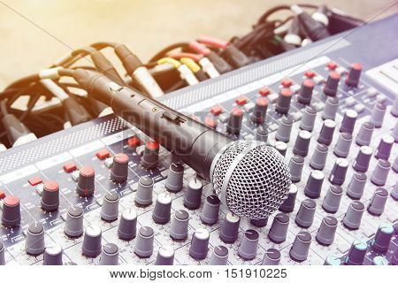 The microphone on sound mixer background. Music instruments or dj concept. Musical equipment microphone with control console.