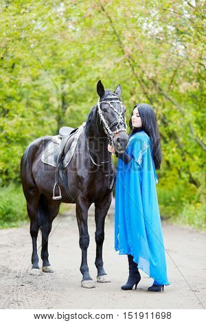 Black-haired woman in blue capote stands with horse in the park.