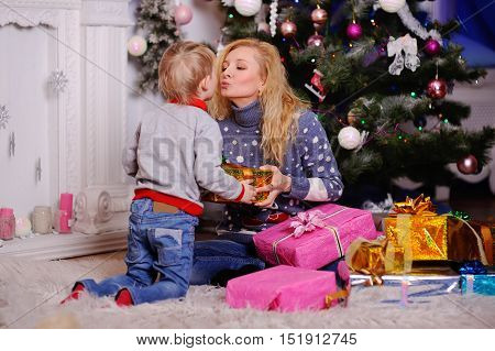 Mom gives a small child a Christmas gift on the Christmas tree background. Christmas presents. Son kisses mother who gives him a gift in a big box