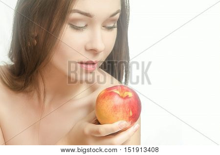 Young tender woman holding a peach in her hand with downcast eyes. White background