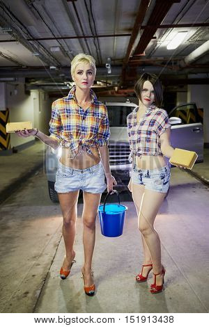 Two young girls in shorts and shirts stand in front of car with sponges and bucket with water at underground parking garage.