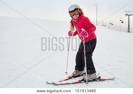 Smiling teenage girl equipped for skiing on snowy slope at ski resort.
