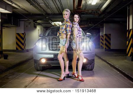 Two young girls in shorts and shirts stands back to back near car at underground parking garage.