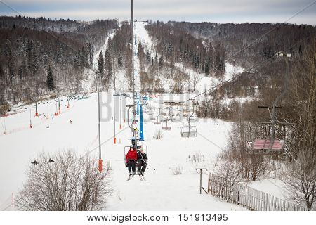 Mother and son rise on cableway on winter day at ski resort.