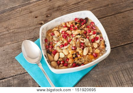 Homemade muesli with pomegranate different nuts and apple sauce on a wooden table