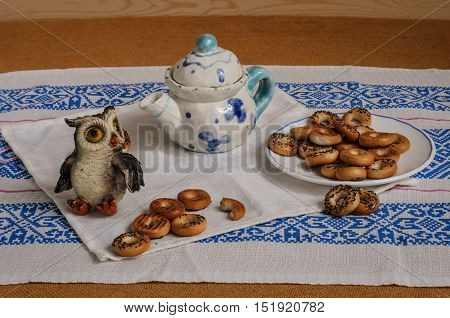 Tea with poppy dryers, toy owlTea with poppy dryers, toy owl chaynk with blue flowers, white plate with a blue stripe np white and blue saofetke