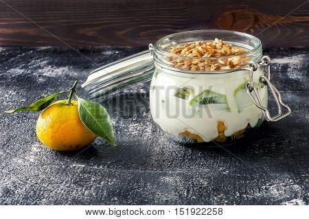 Sweet parfait with kiwi, yogurt and muesli on dark table