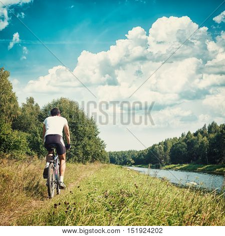 Rear View of a Cyclist Riding a Bike on River Bank. Healthy Lifestyle and Leisure Activity Concept. Toned and Filtered Instagram Styled Photo with Copy Space.