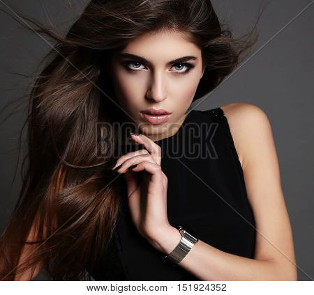 fashion studio photo of gorgeous woman with dark hair and bright makeup in elegant black dress