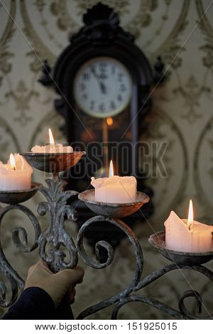Burning candles in old candlestick in human hand and clock on the wall in room.