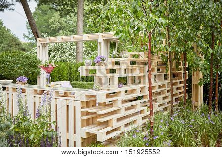 Wooden alcove made of pallets outdoor in summer park.