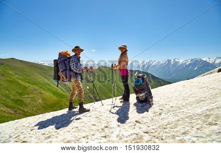 Kazakhstan Shymkent on June 12 2016. Young man and the woman with backpacks and ski sticks stand on snow highly in mountains and look in a distance in a bright sunny day. editorial