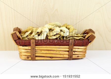 Dehydrated apple slices in a wicker basket against a wooden background
