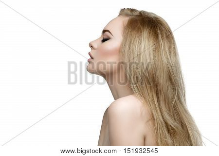 Profile portrait of beautiful young woman with messy long blond hair and bright makeup. Beauty shot. Isolated over white background. Copy space.