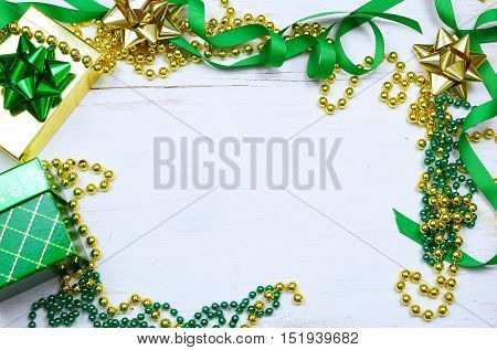 Christmas gifts colorful ribbons and bows with green and gold beads form a border around a rustic white washed wooden table top. Overhead perspective. Copy space