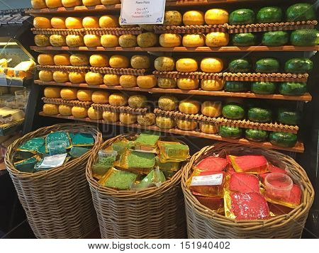 AMSTERDAM, NETHERLANDS - MAY 3, 2016: Original cheese wheels on the shelves in cheese shop in Amsterdam, Netherlands.