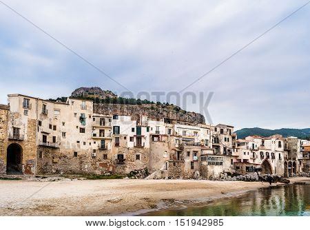 View on habour and old houses in Cefalu at sunset, Sicily. Beautiful townscape of old italian town. Travel photography.
