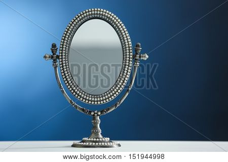 Female mirror on color background