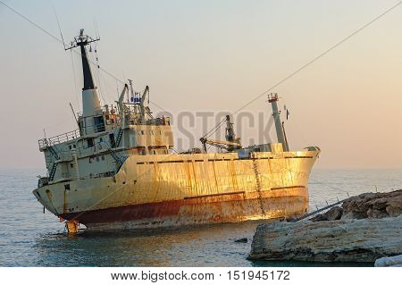 Cargo ship aground near rocky coast in sunset light