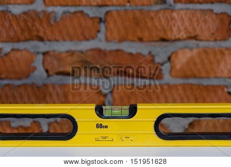 Yellow building level isolated on brick background.
