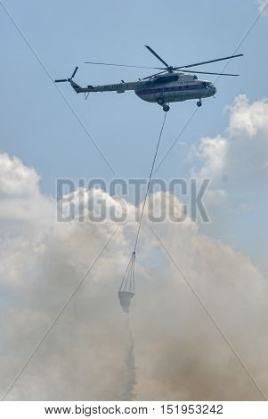 Nizhniy Tagil, Russia - July 12. 2008: MI-8 helicopter of Emergency situations Ministry flies with water tank for fire extinguishing