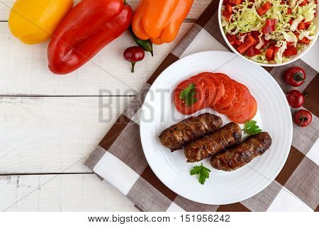 Juicy grilled rolls of minced meat wrapped in bacon with fresh tomato and a light salad of Chinese cabbage and bell pepper. poster