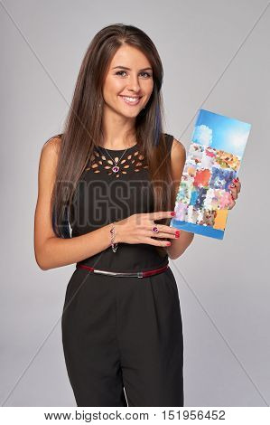 Smiling business woman showing an advertising brochure