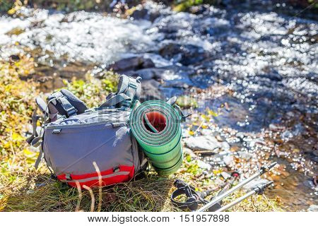 Red-gray rucksack and trekking poles at river background.