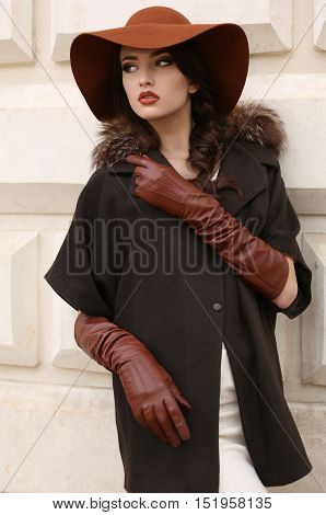 fashion outdoor photo of gorgeous woman with dark hair in elegant luxurious coat wool hat and leather gloves walking by autumn city