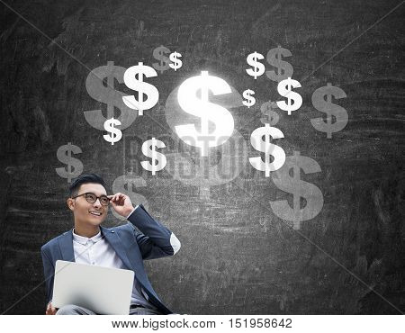 Cheerful Asian buisnessman in glasses sitting near blackboard with dollar sketches on it. Concept of earning big bucks.