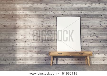 Framed vertical poster is standing on narrow table with drawers against board wall. 3d rendering. Mock up