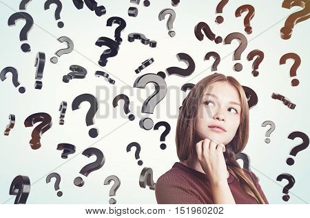 Portrait of young woman in brown sweater standing near question marks floating in the air. Concept of looking for the answer. Toned image