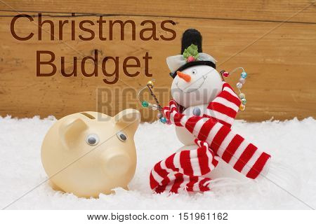 Having a Christmas Budget Piggy bank and Snowman with scarf on snow with a weathered wood background with text Christmas Budget